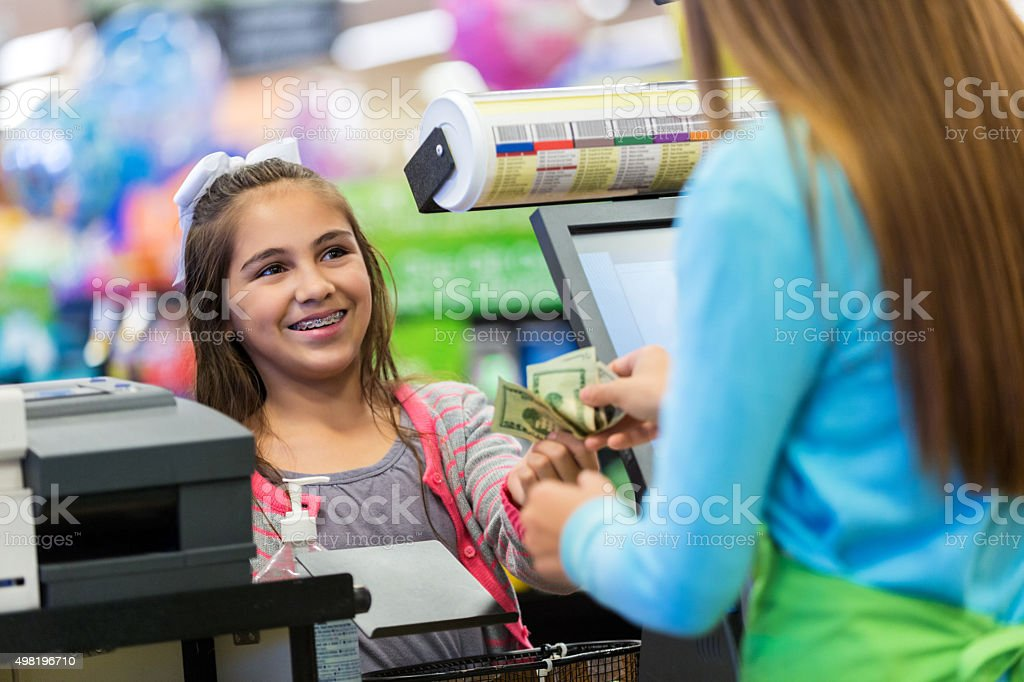 Little girl paying for purchases with cash in local store stock photo