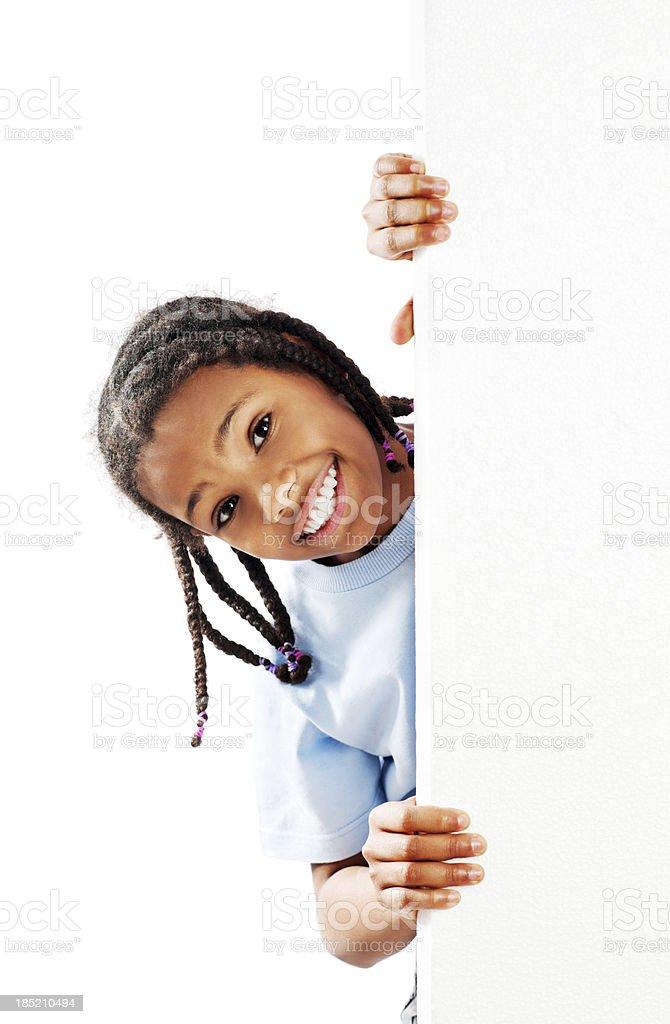 Little girl peeking behind Whiteboard. stock photo