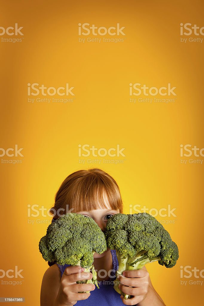 Little Girl Peeking Out From Behind Broccoli royalty-free stock photo