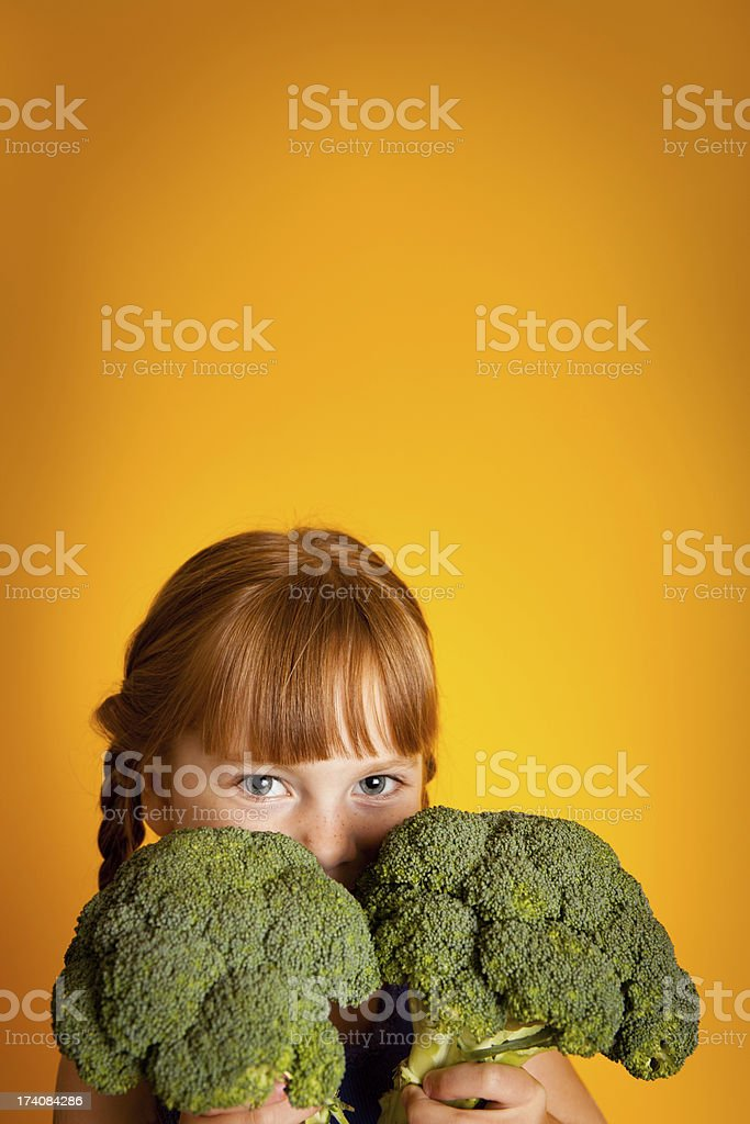 Little Girl Peeking Out From Behind Bunches of Broccoli royalty-free stock photo