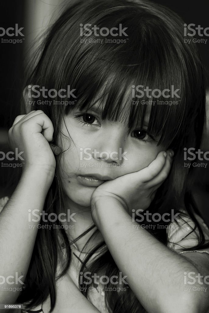 A little girl photographed in black and white looking sad stock photo