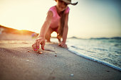 Little girl picking up sea shells at the beach