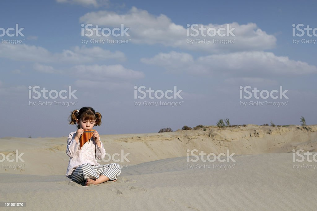 little girl play music on pan pipe stock photo