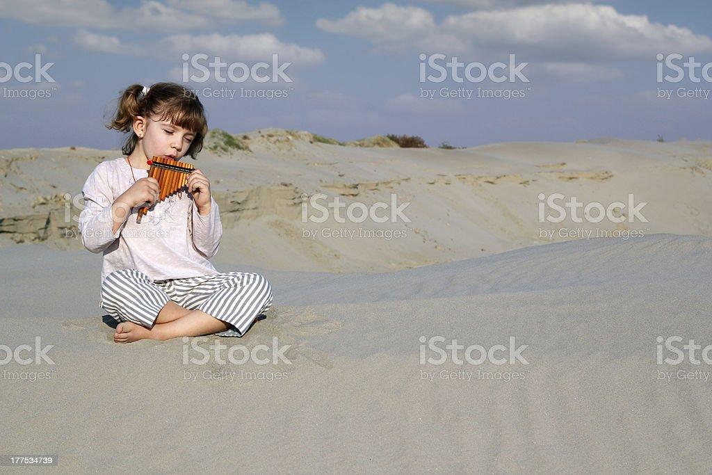 little girl play panpipe in desert stock photo