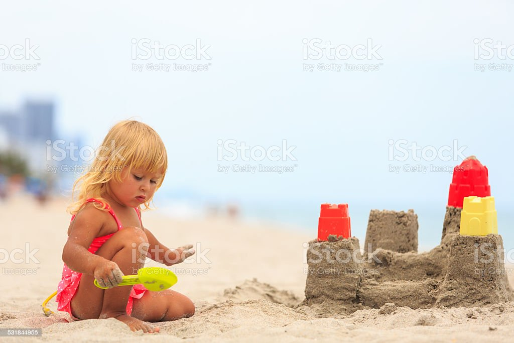 little girl play with sand on beach stock photo