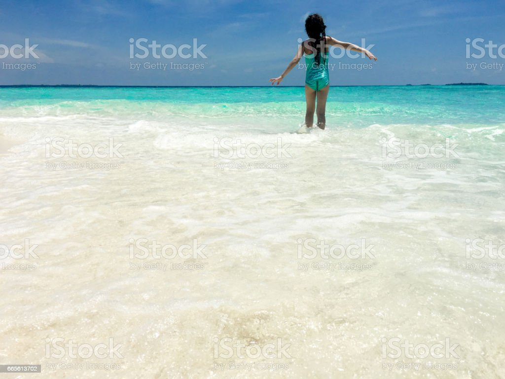 Little Girl Play With Waves On Tropical Beach stock photo