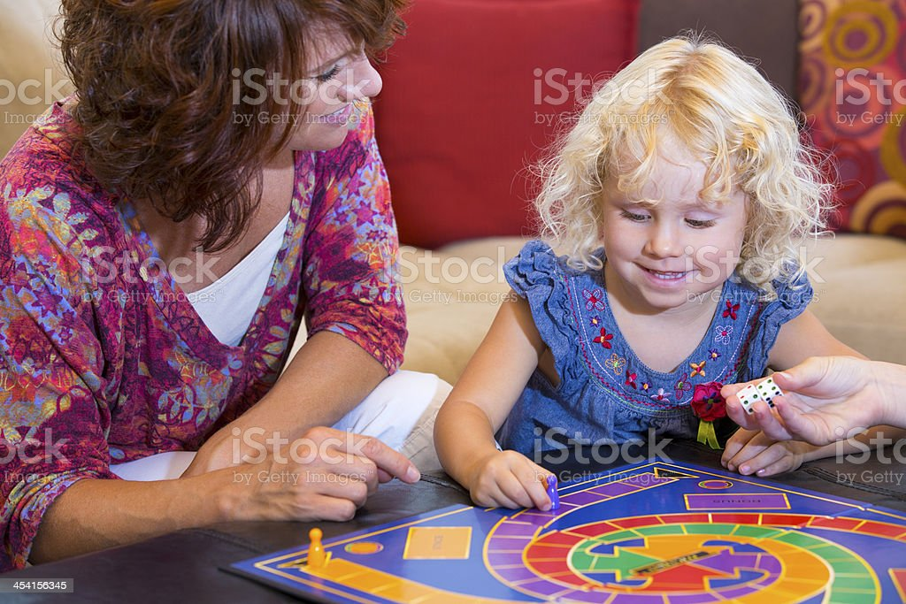 Little girl playing a board game with her mom stock photo