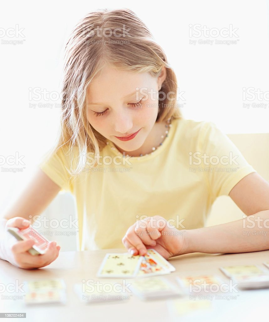 Little girl playing a game of solitaire stock photo
