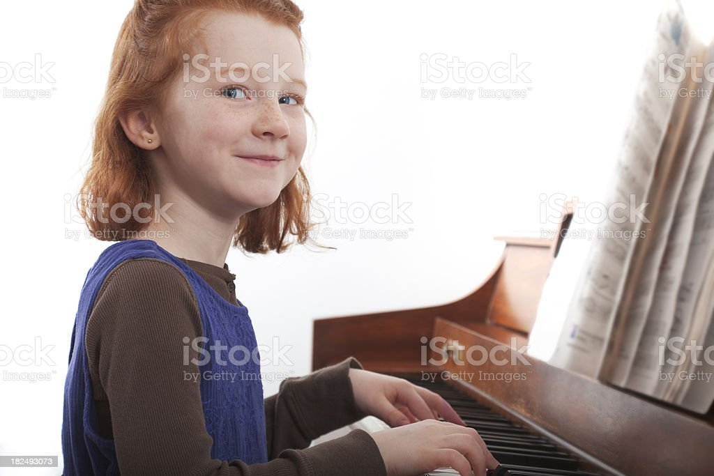 little girl playing a piano royalty-free stock photo
