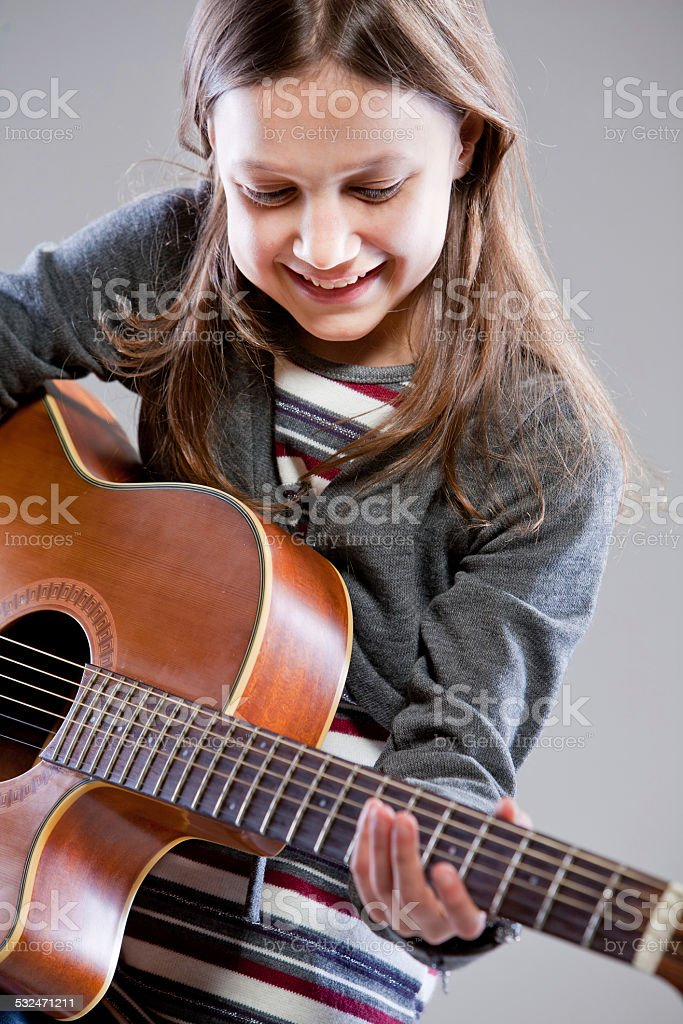 little girl playing acoustic guitar stock photo
