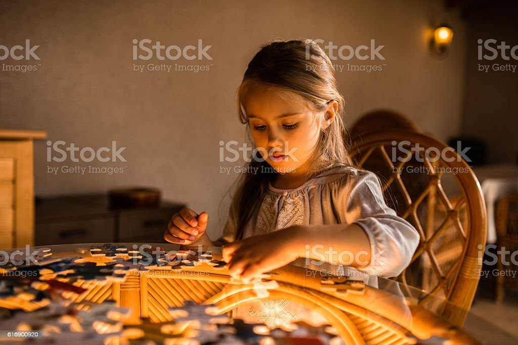 Little girl playing and connecting puzzles indoors. stock photo