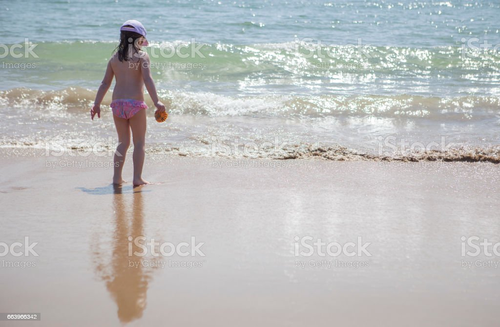 Little girl playing at beach shore stock photo