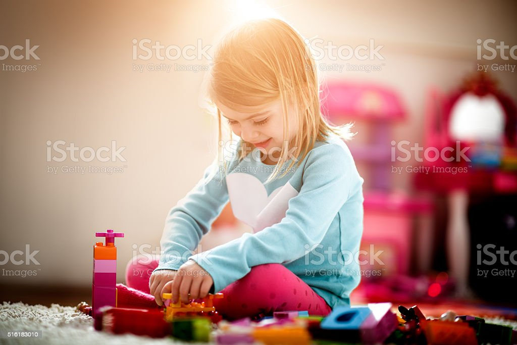 Little girl playing at home stock photo