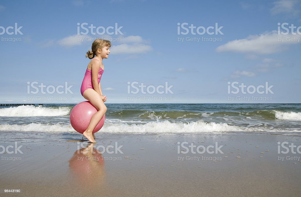 Little girl playing at the beach stock photo