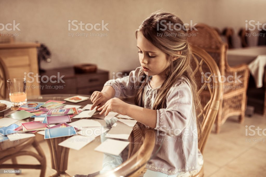 Little girl playing card memory game at the table. stock photo