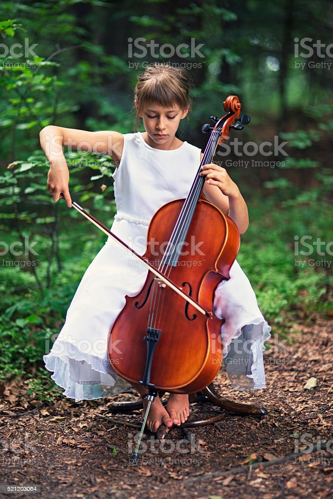 Little girl playing cello in forest stock photo