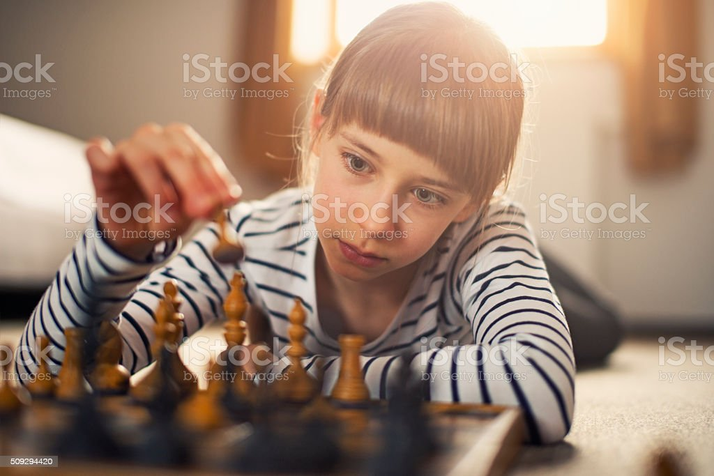 Little girl playing chess stock photo