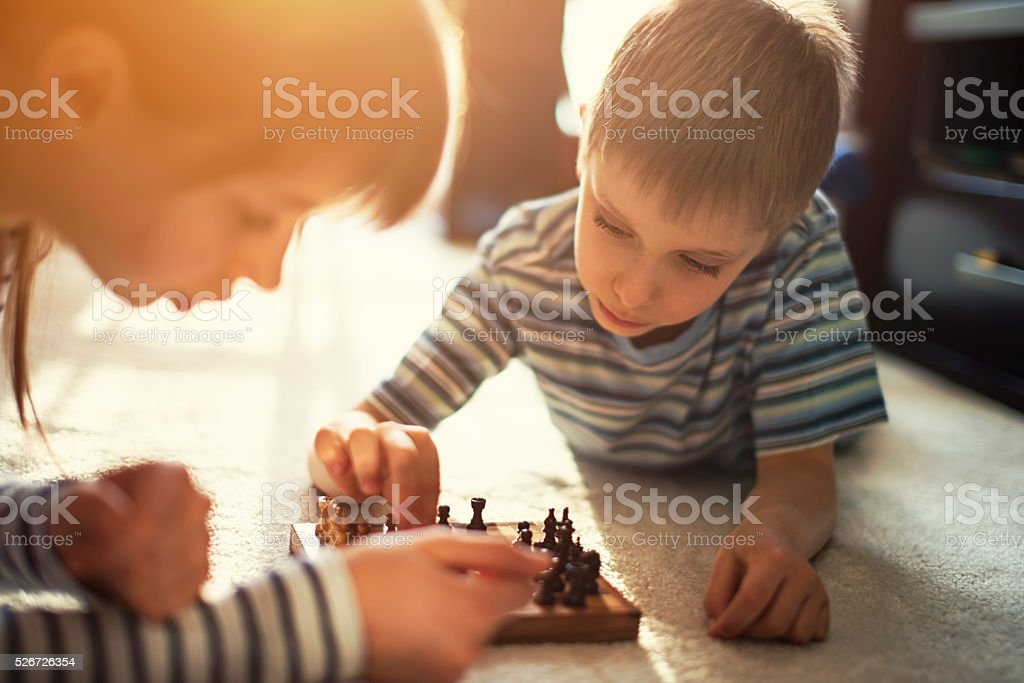 Little girl playing chess with her brother stock photo