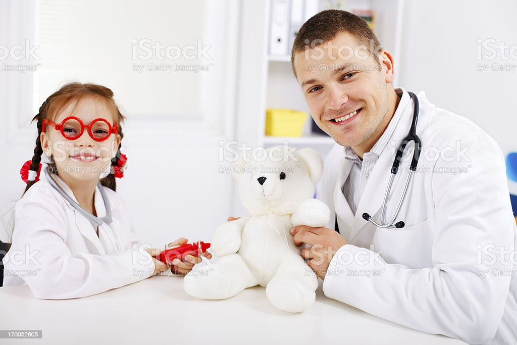 Little girl playing doctor with pediatrician royalty-free stock photo