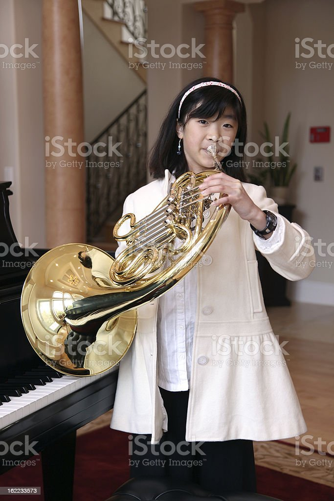 Little Girl Playing French Horn royalty-free stock photo