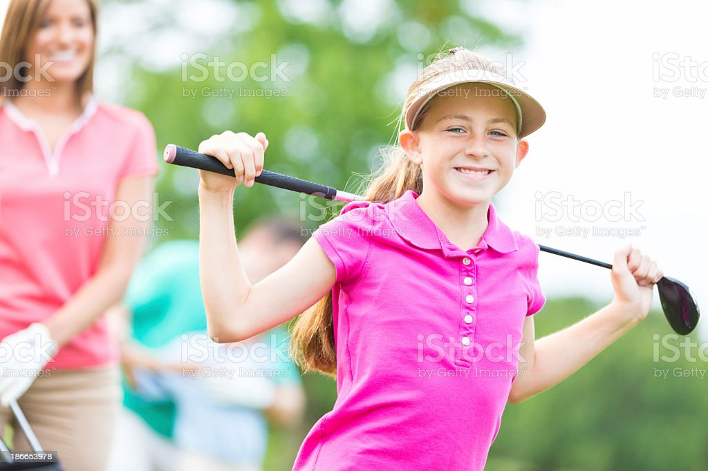 Little girl playing golf with family on country club course stock photo