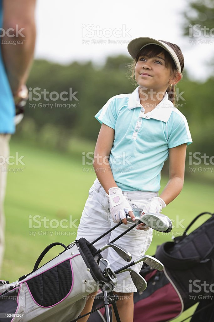 Little girl playing golf with father at country club royalty-free stock photo
