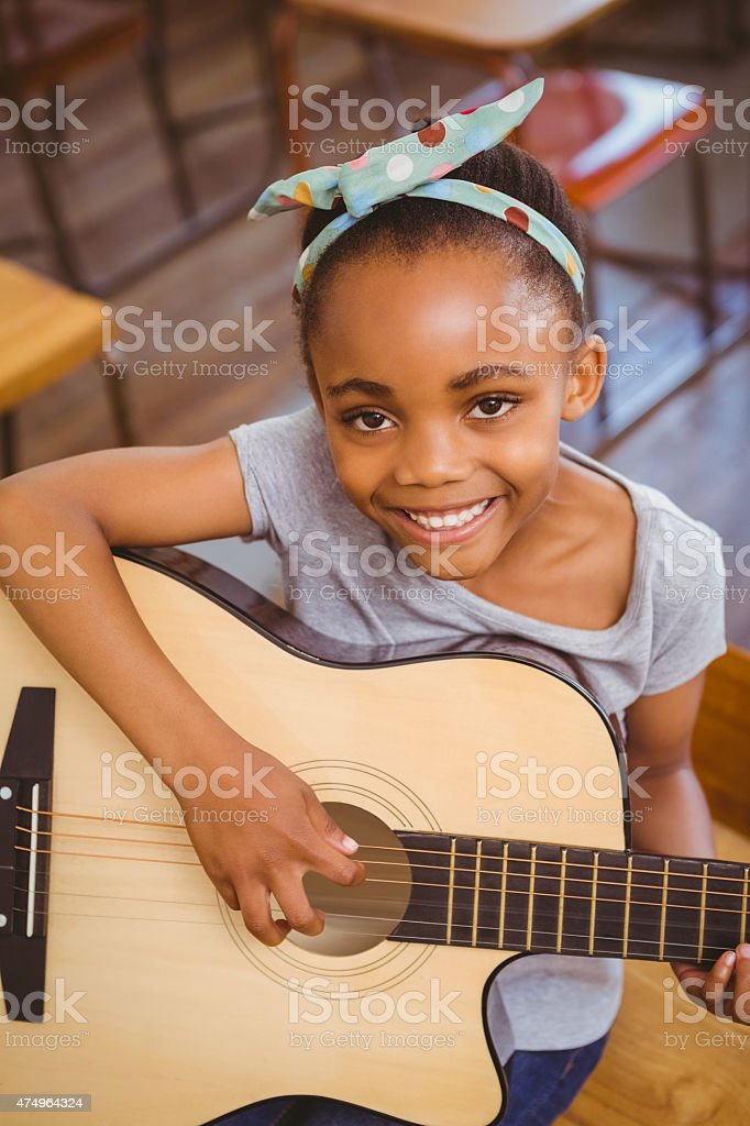 Little girl playing guitar in classroom stock photo