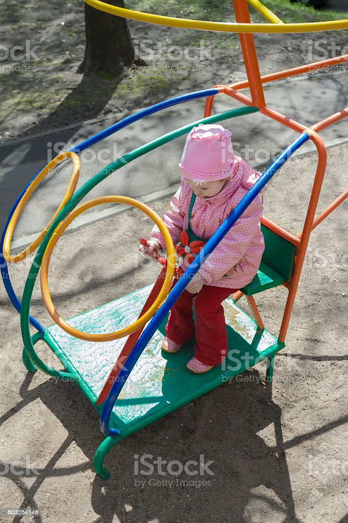 Little girl playing handling game monkey bar on outdoor playground stock photo