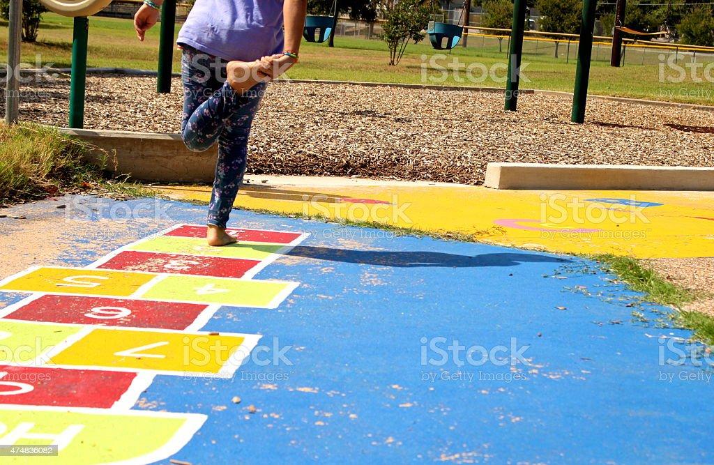 Menina brincando em um Playground Jogo da amarelinha foto royalty-free