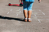 little girl playing hopscotch on playground