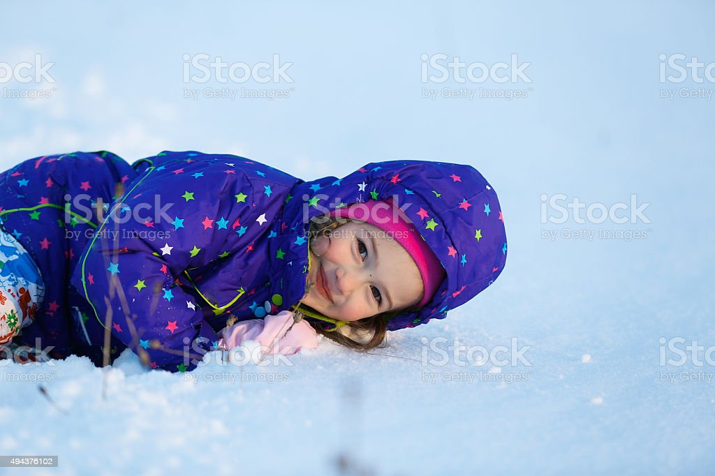 Little girl playing in fresh snow stock photo