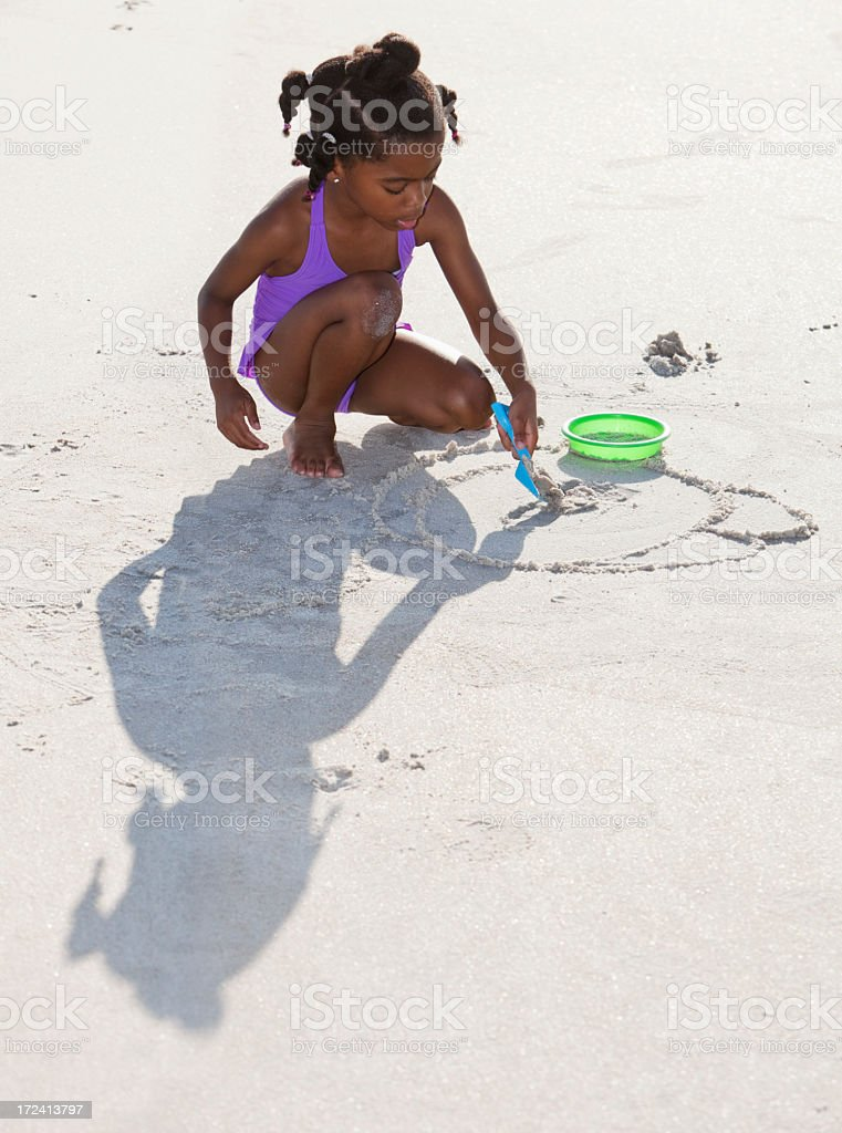 Little girl playing in sand at beach stock photo