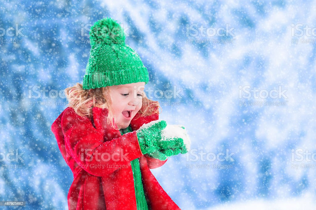 Little girl playing in snowy park stock photo