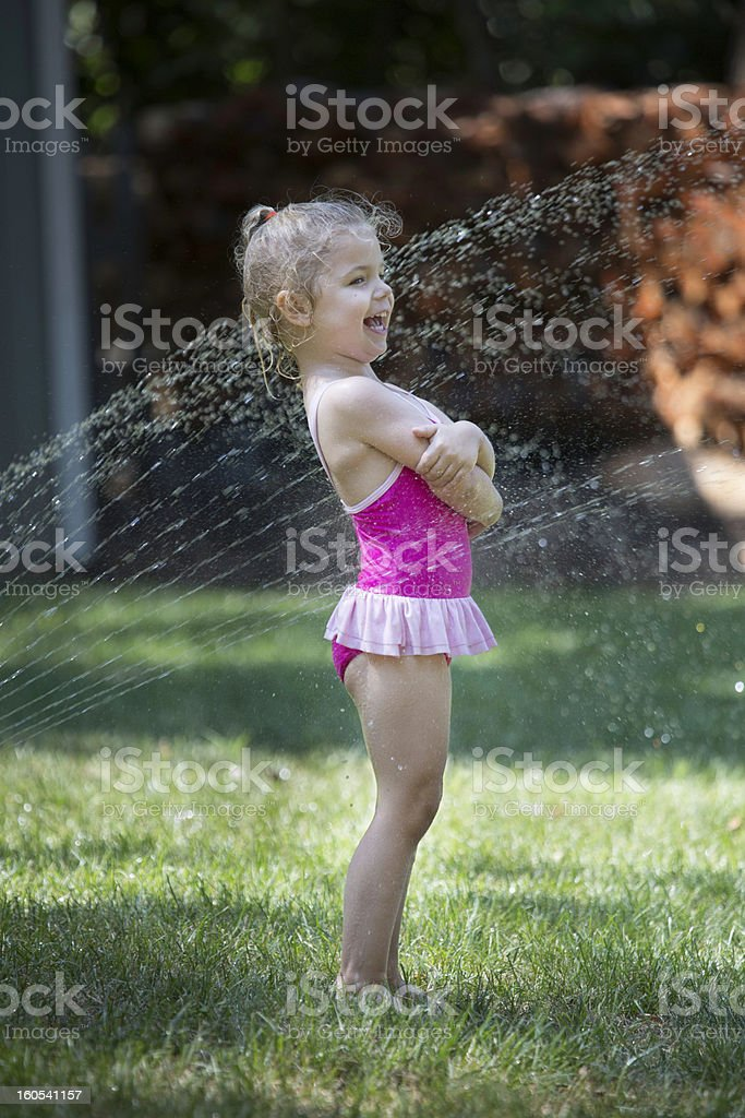 Little girl playing in sprinkler royalty-free stock photo