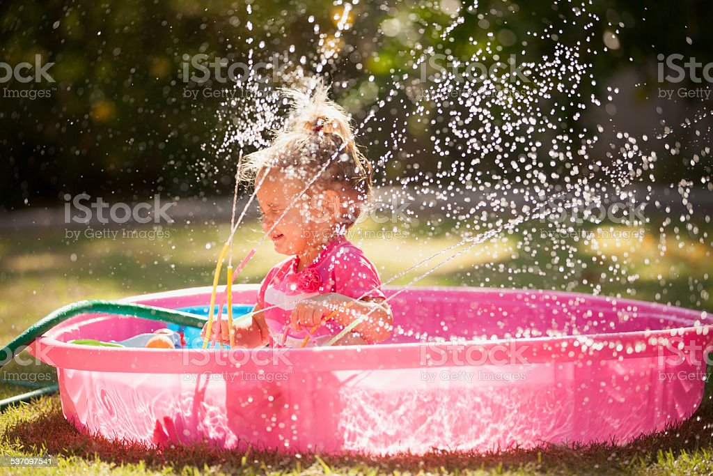 Little Girl Playing in Sprinkler stock photo