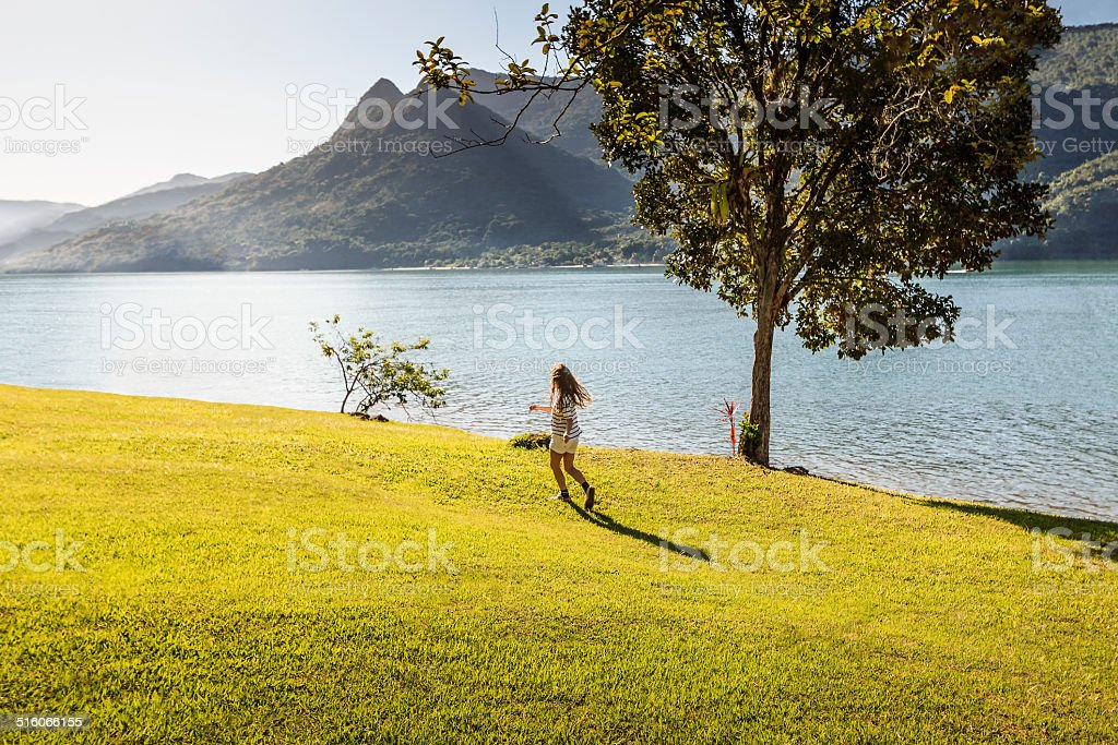 Little Girl Playing in Sunny Day Near Fiord in Paraty stock photo