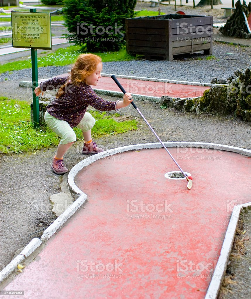 Little girl playing mini golf, her way royalty-free stock photo