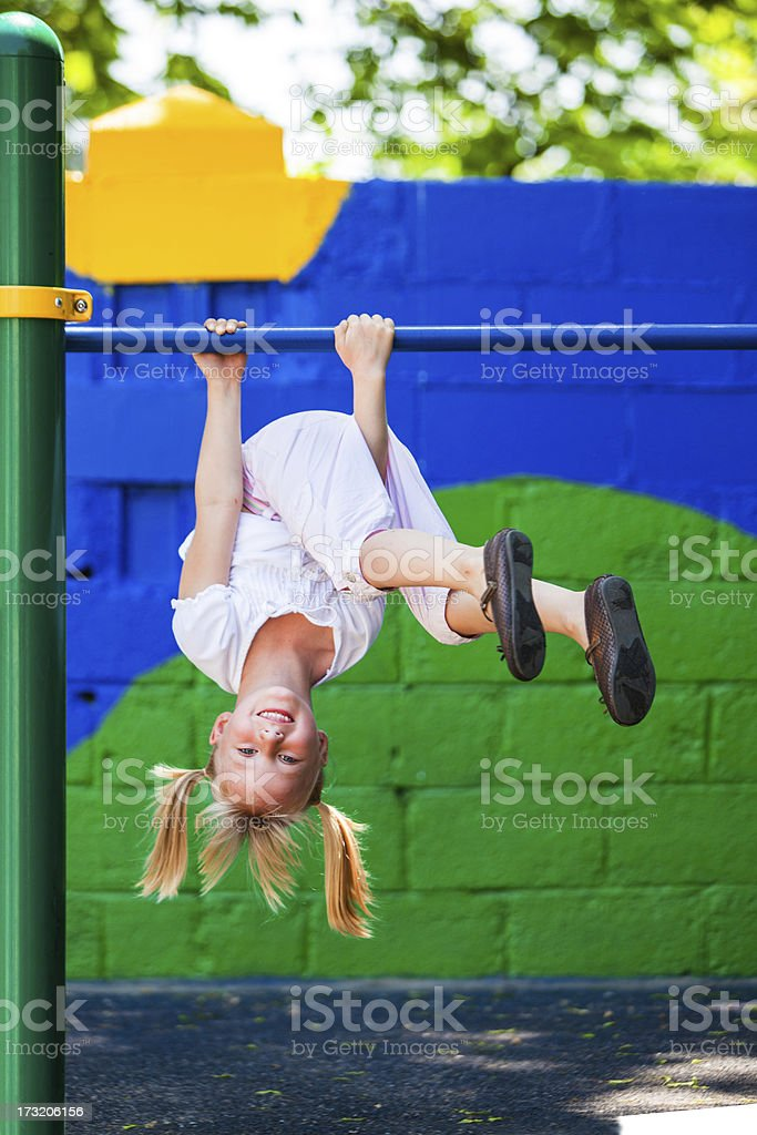 Little girl playing on a jungle gym stock photo