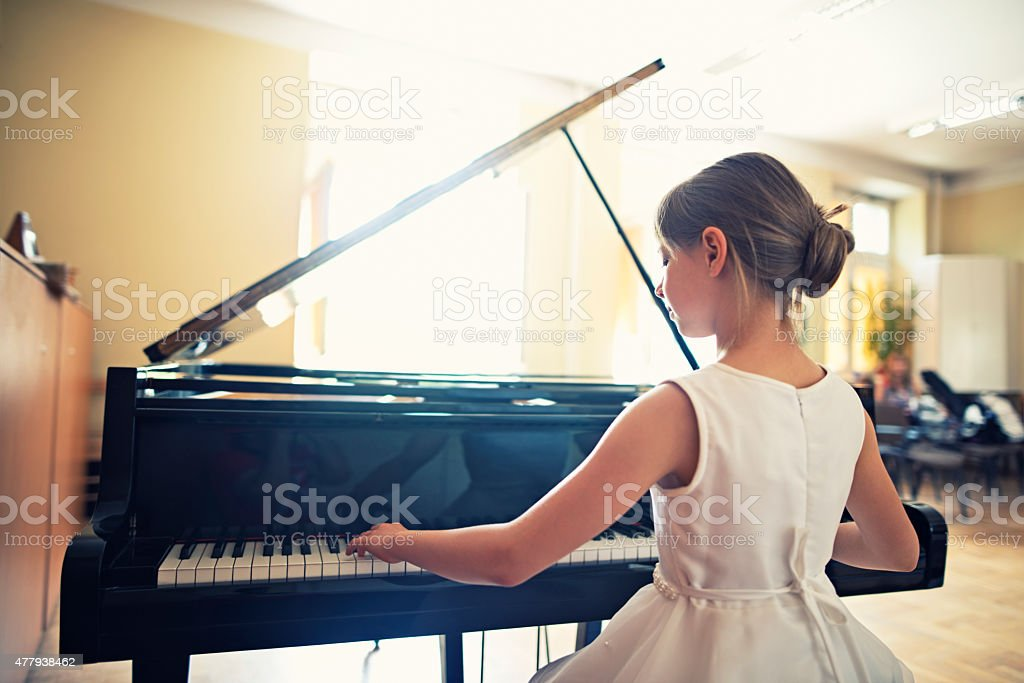 Little girl playing on grand piano stock photo