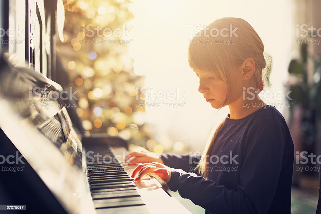 Little girl playing on grandmother piano stock photo