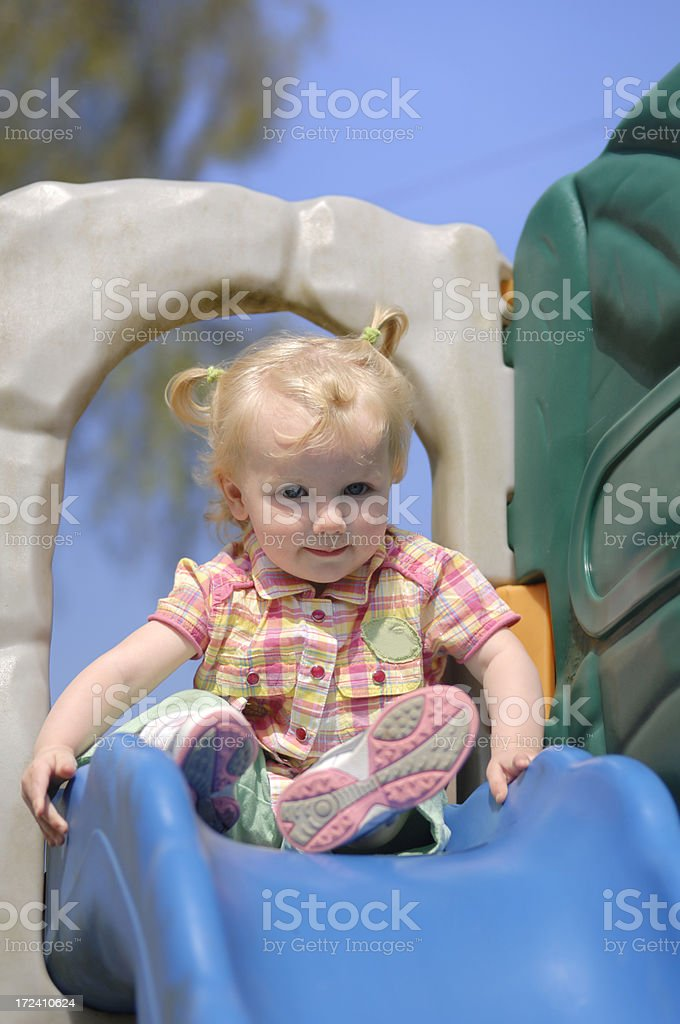 little girl playing on shute stock photo