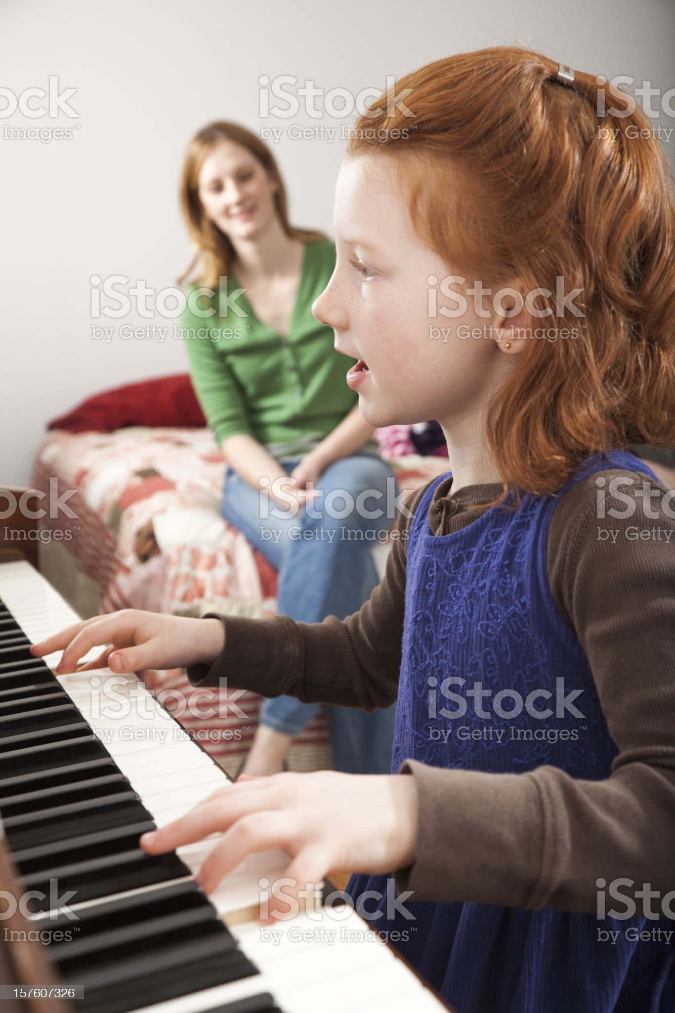 little girl playing piano while her mother watches and listens royalty-free stock photo