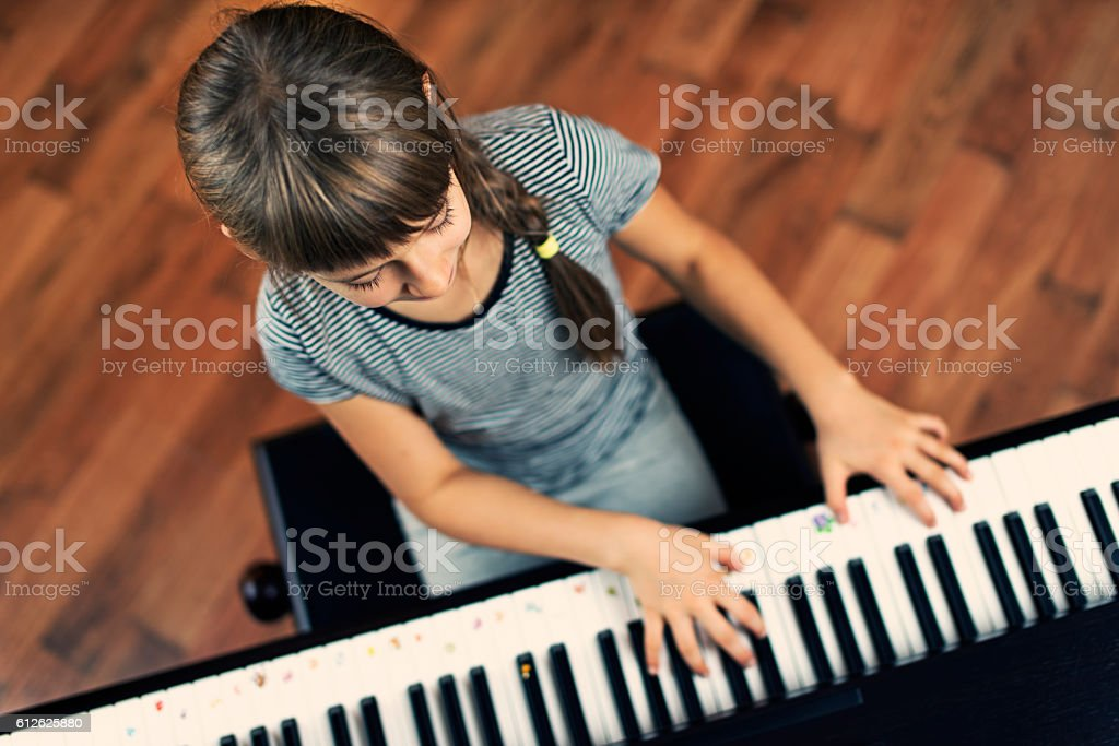 Little girl playing the digital piano stock photo