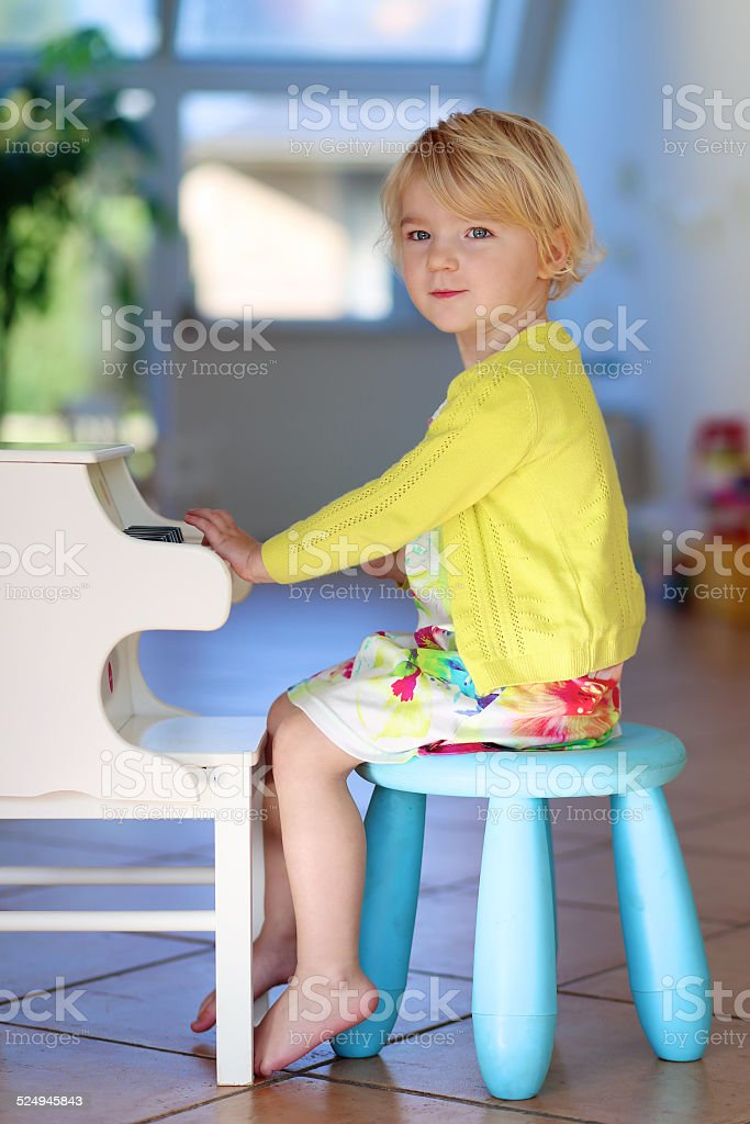 Little girl playing toy piano at home stock photo
