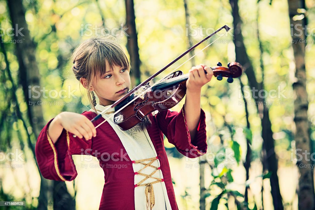 Little girl playing violin outdoors stock photo