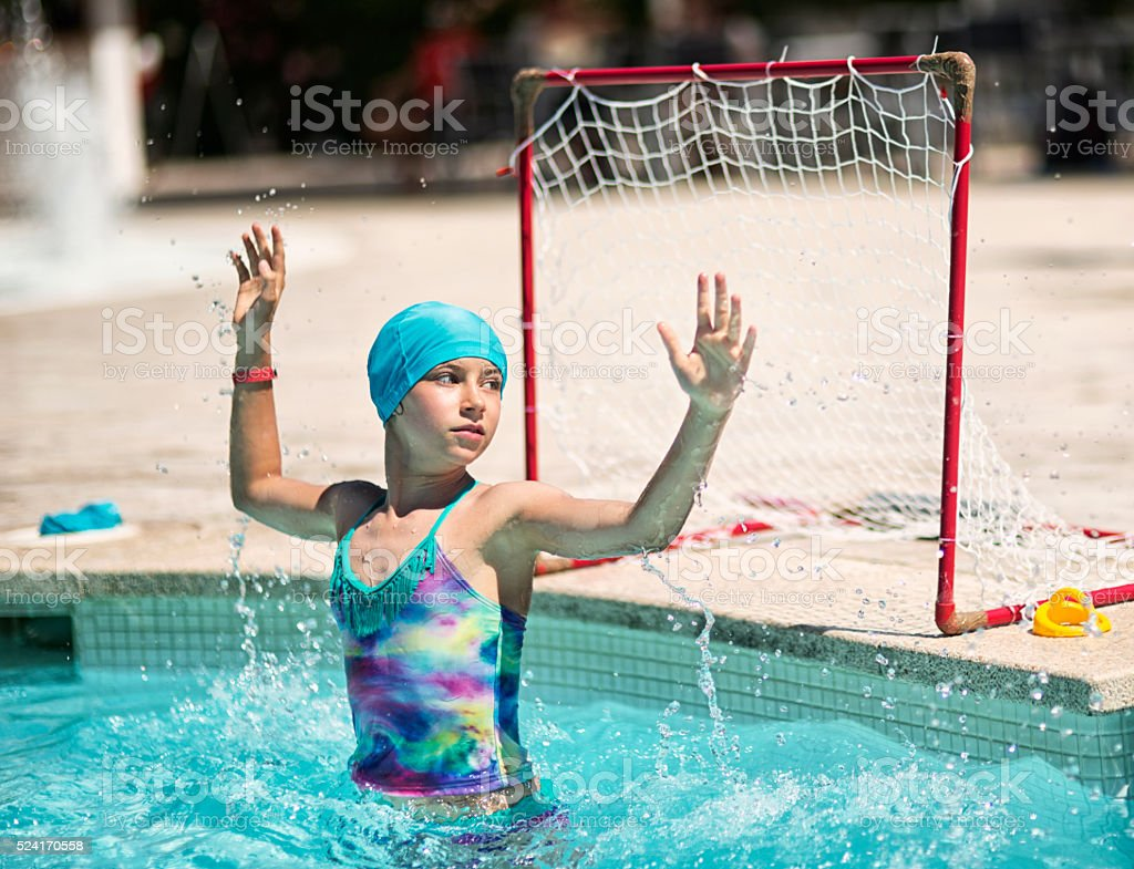 Little girl playing water polo in outdoors swimming pool. stock photo