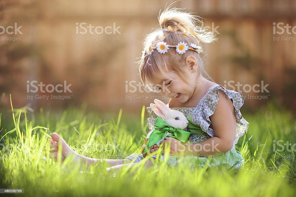 Little girl playing with a bunny on the grass stock photo