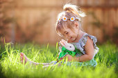 Little girl playing with a bunny on the grass