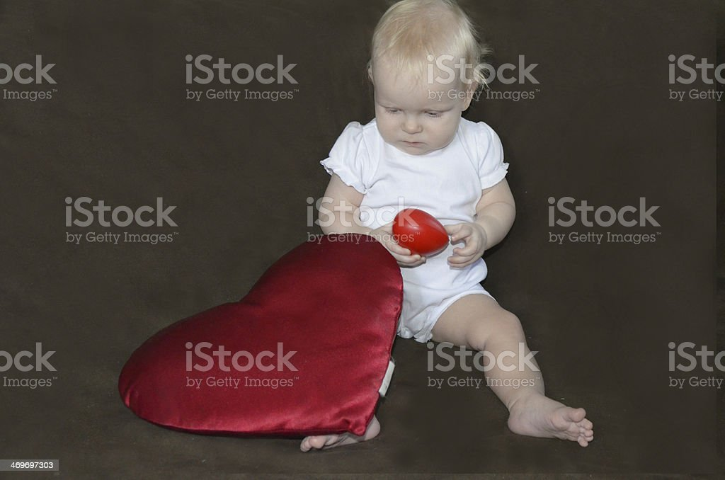 Little girl playing with a red heart on gray background royalty-free stock photo