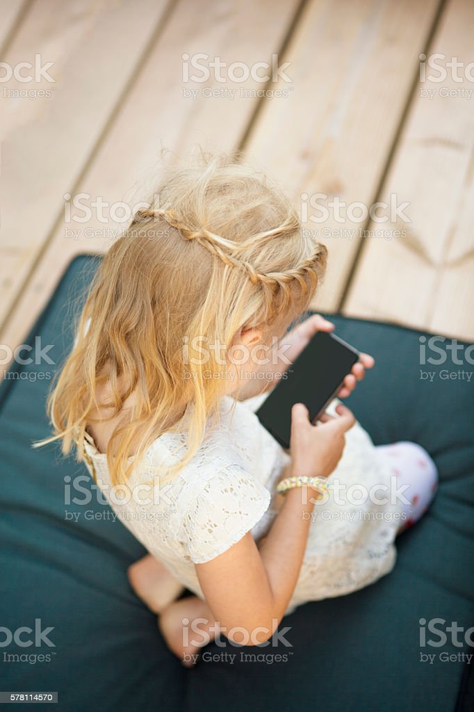 little girl playing with a smartphone stock photo